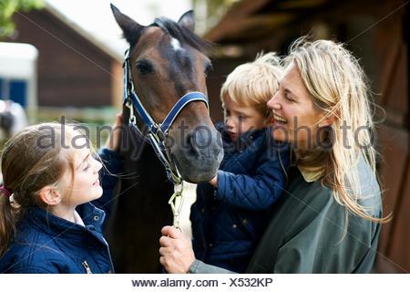 Femme mature avec son fils et sa fille petting horse Banque D'Images
