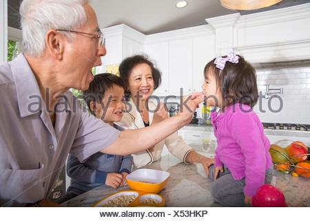 Grand-père à l'alimentation des tout-petits en-cas petite-fille cuisine Banque D'Images
