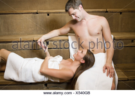Woman resting head on boyfriend's lap in sauna Banque D'Images