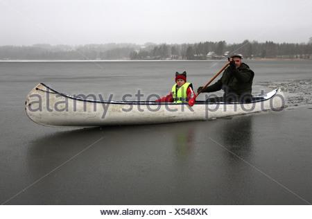 Homme et enfant assis dans un canoë sur un lac gelé Banque D'Images