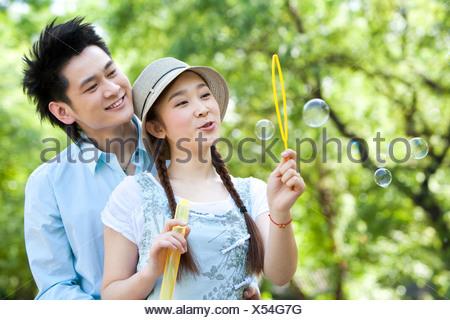 Heureux couple faisant des bulles dans le parc Banque D'Images