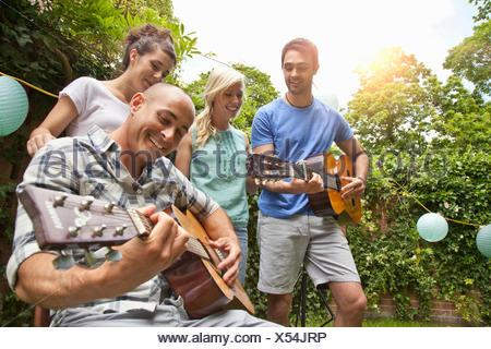 Les amis masculins playing acoustic guitar dans le jardin pour les amies Banque D'Images