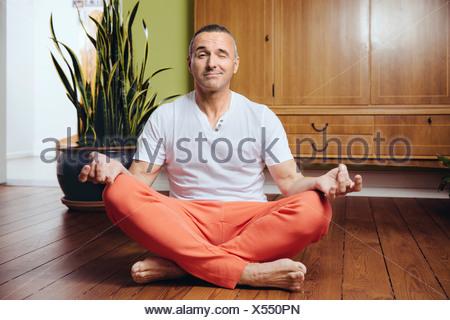 Allemagne, Bonn, Mature man in a yoga pose, assis sur le plancher en bois de sa maison Banque D'Images
