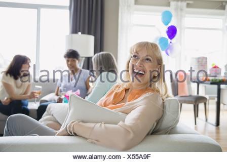 Woman laughing at party dans la salle de séjour Banque D'Images