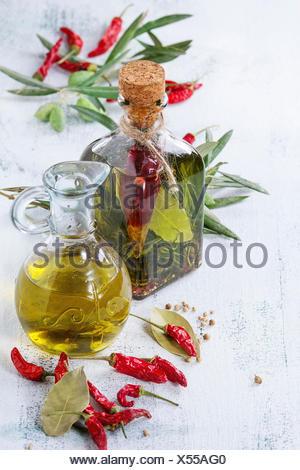 Le flacon en verre et carafe d'huile d'olive épicée au romarin, Red Hot Chili Peppers et le laurier debout avec la direction générale des olives over white Banque D'Images