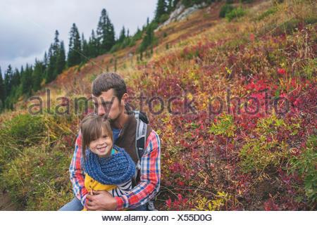 Père assis avec sa fille sur une montagne Banque D'Images