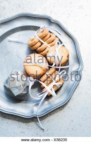 Vue de dessus de biscuit à égalité avec ruban blanc sur un plat de service en argent