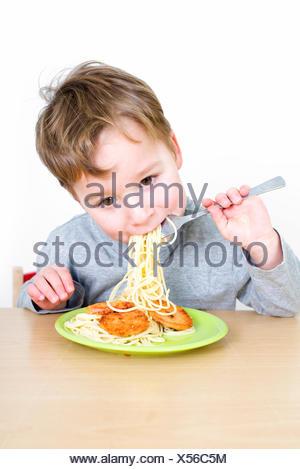 Petit garçon mange du spaghetti Banque D'Images