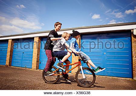 Garçon donnant deux amis une balade en vélo Banque D'Images