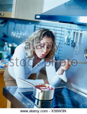 Woman leaning on la cuisinière et dégustation de soupe de tomate avec une cuillère Banque D'Images