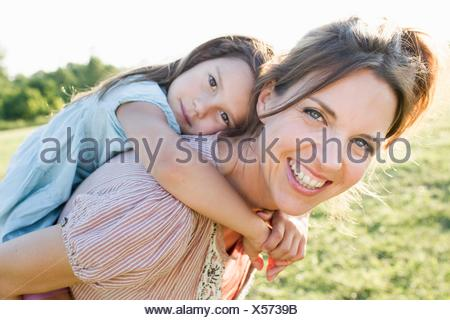 Young woman giving daughter piggy back ride in park Banque D'Images