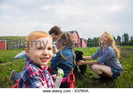 Smiling boy en wagon in rural field Banque D'Images