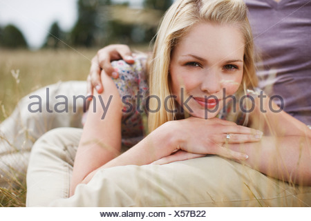 Close up portrait of smiling woman man's lap in rural field Banque D'Images