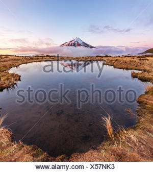 Reflet dans le lac rose Pouakai Tarn, nuages autour du Mont Taranaki ou Mont stratovolcan Egmont au coucher du soleil, Parc National d'Egmont Banque D'Images
