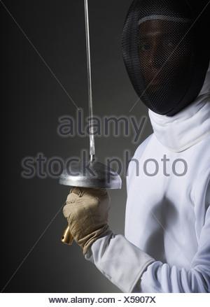Portrait de studio de fencer holding fencing foil Banque D'Images