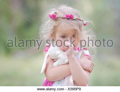 Portrait d'une fille suçant son pouce et embrassant son jouet de lapin doux, Californie, États-Unis Banque D'Images
