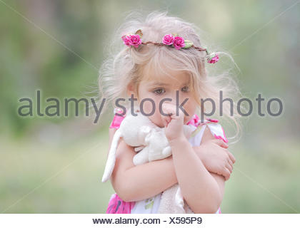USA, Little girl (4-5) sucking thumb et serrant doudou en plein air Banque D'Images
