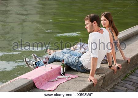 Couple assis à la corniche d'un canal, Paris, Ile-de-France, France Banque D'Images
