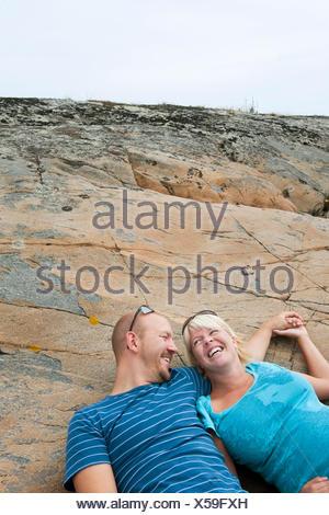 La Suède, Halland, Onsala, Couple lying on rock Banque D'Images