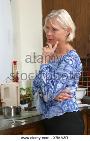50 femme pense en cuisine Banque D'Images