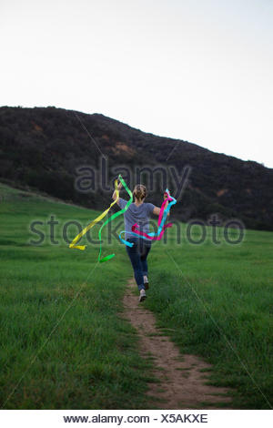 Vue arrière du young woman running on path holding up dance ribbons Banque D'Images
