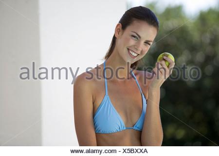 Une femme dans un bikini de manger une pomme Banque D'Images