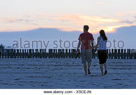 Jeune couple de prendre une marche sur la plage au coucher du soleil, Zoutelande, presqu'île de Walcheren, province de Zélande, Pays-Bas, Benelux Banque D'Images