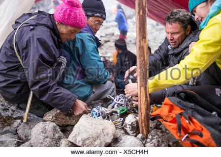 Les membres de l'expédition vérifier l'équipement avec l'aide de guides locaux. Banque D'Images