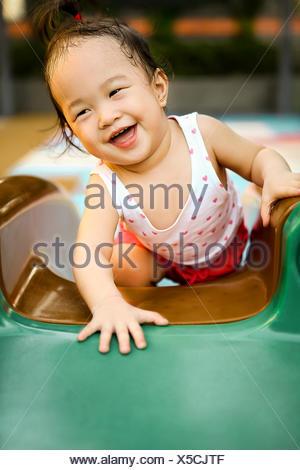 Portrait d'une fille heureuse sur une glissade dans une aire de jeux intérieure Banque D'Images