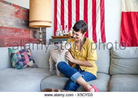 Young woman petting dog on sofa du salon Banque D'Images