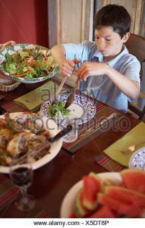 Portrait d'un jeune garçon assis à une table à manger Banque D'Images