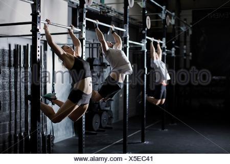 Les jeunes adultes mâles et femelles sur le mur d'entraînement de sport en bar