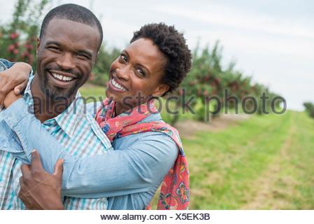 Un verger de pommes biologiques. Un couple hugging and smiling at the camera. Banque D'Images