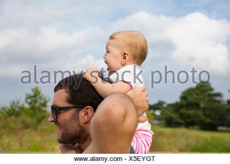 Mid adult man carrying baby fille sur les épaules Banque D'Images
