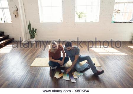 Jeune couple assis sur un tapis dans un loft à la recherche à des échantillons de couleur Banque D'Images