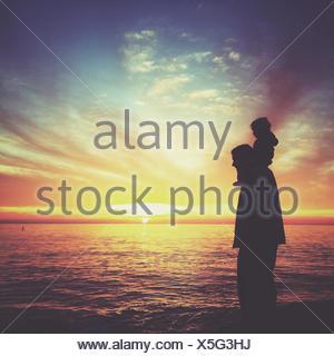 Silhouette de garçon assis sur les épaules de son père, Laguna Beach, en Californie, l'Amérique, USA Banque D'Images