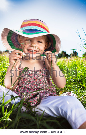 Girl wearing sunhat in grass Banque D'Images