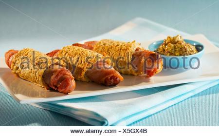 Les porcs dans des couvertures avec bacon et moutarde Banque D'Images