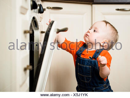 Bébé curieux regardant à travers le verre de cuisine four Banque D'Images