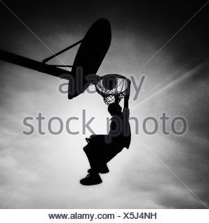 Silhouette de garçon à jouer au basketball slam dunk de notation Banque D'Images