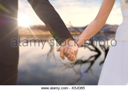 Image composite de mid section of senior couple holding hands in park Banque D'Images