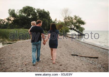 Vue arrière du couple strolling along beach avec l'homme tout-petit fils, le lac Ontario, Canada Banque D'Images