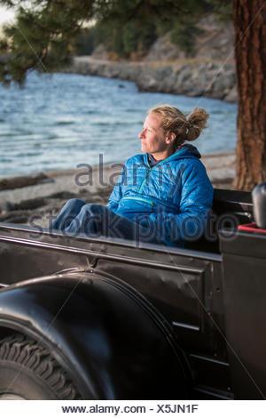Femme assise en regardant le coucher du soleil, camion rénové Lac Payette, McCall, New York, USA