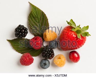 Mélange de petits fruits: fraises, framboises rouges et or, mûres, myrtilles et cranberry avec feuilles, sur blanc. Banque D'Images