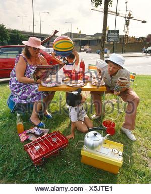 Famille assis sur un rond-point, faire un pique-nique Banque D'Images