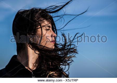 Jeune femme à la recherche sur le côté avec les cheveux au vent Banque D'Images