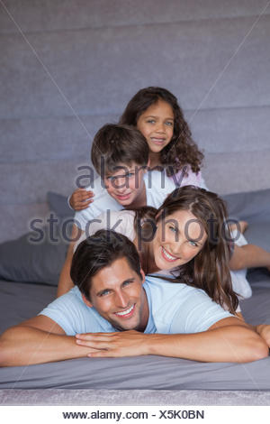 Famille heureuse de jouer ensemble sur le lit Banque D'Images