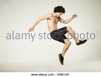 Torse nu African man jumping Banque D'Images