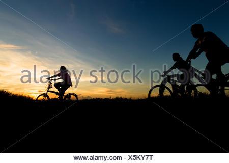 Silhouette of family vélo au coucher du soleil Banque D'Images