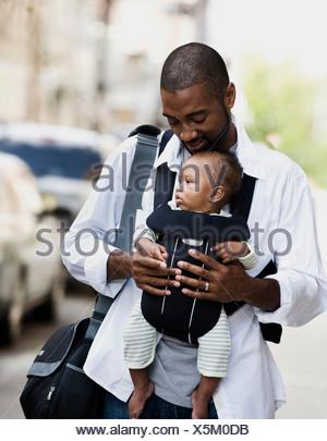 Mid adult man carrying son en porte-bébé Banque D'Images